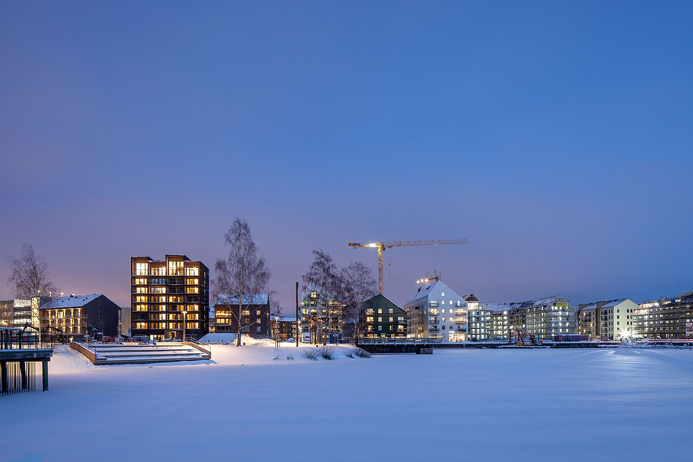 Tall wooden buildling at night with snow