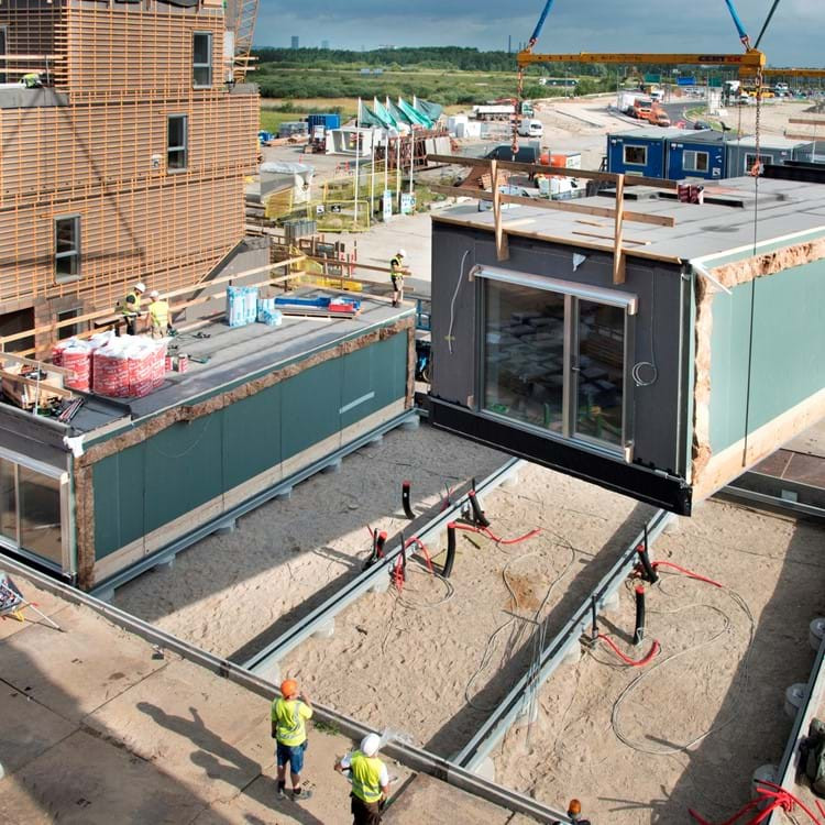 A modular housing timber container is placed on a construction site