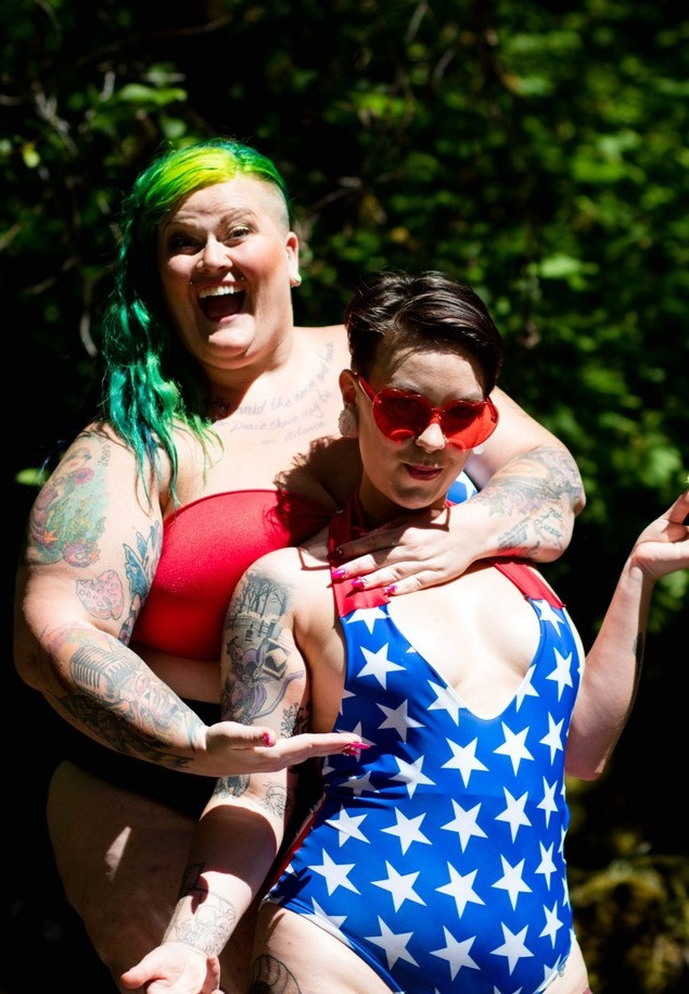 Two heavily tattooed white afab models wear patriotic swimsuits in the sun.