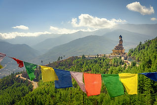 Paro Buddha with prayer flags in foregro