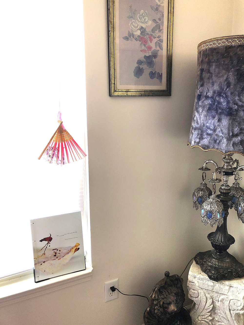 """Image of book """"the CLOUD that fell from the sky"""" in a window below a fan and purple, velvet vintage lamp."""