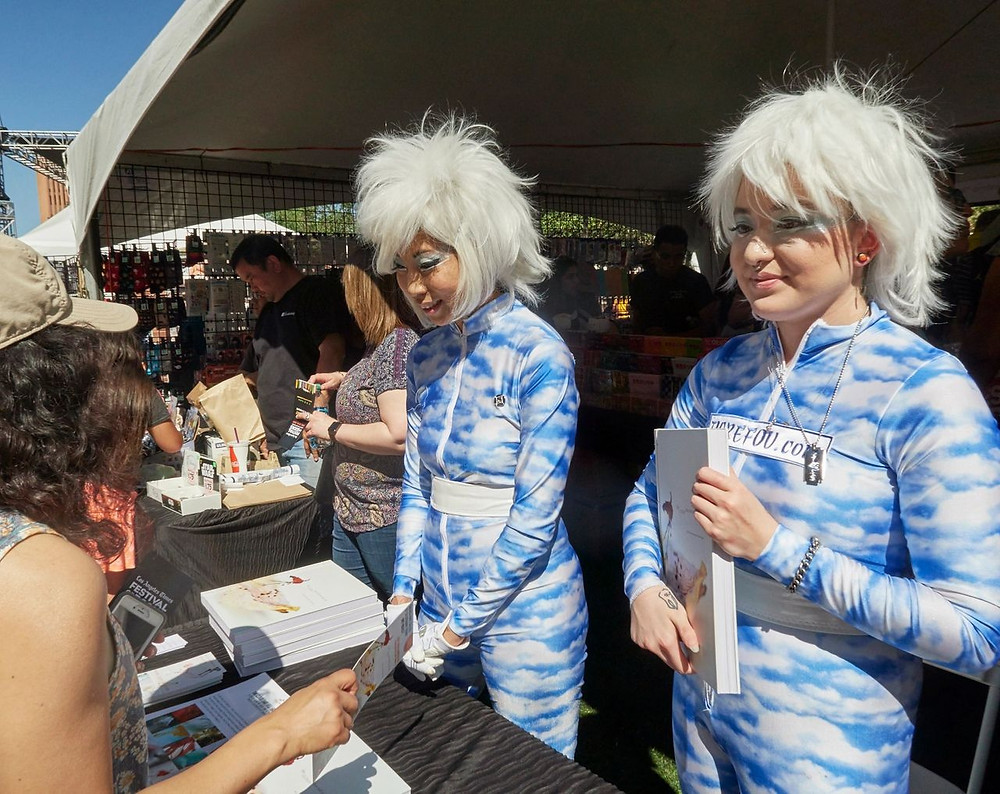 Judy Choi and Phoenix Brown of Tigrefou Editions and Kinokuniya booth chat with a festival goer at the L.A. Times Book Festival