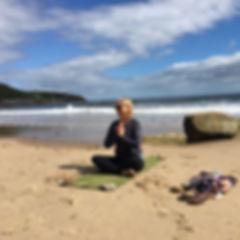 Liz on beach namaste.JPG