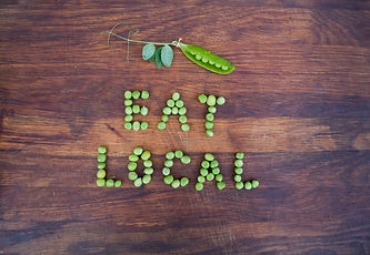 "Sign ""Eat Local"" made of green peas and"