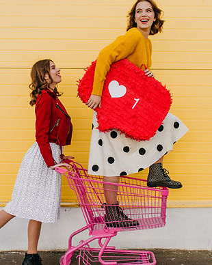 Adorable sisters having fun during shopping. Two glamorous girls posing with heart symbol.