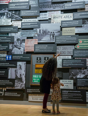 The Wall of Laws, a 12' tall installation featuring the laws used to enforce apartheid, sign reproductions, photographs and artifacts.