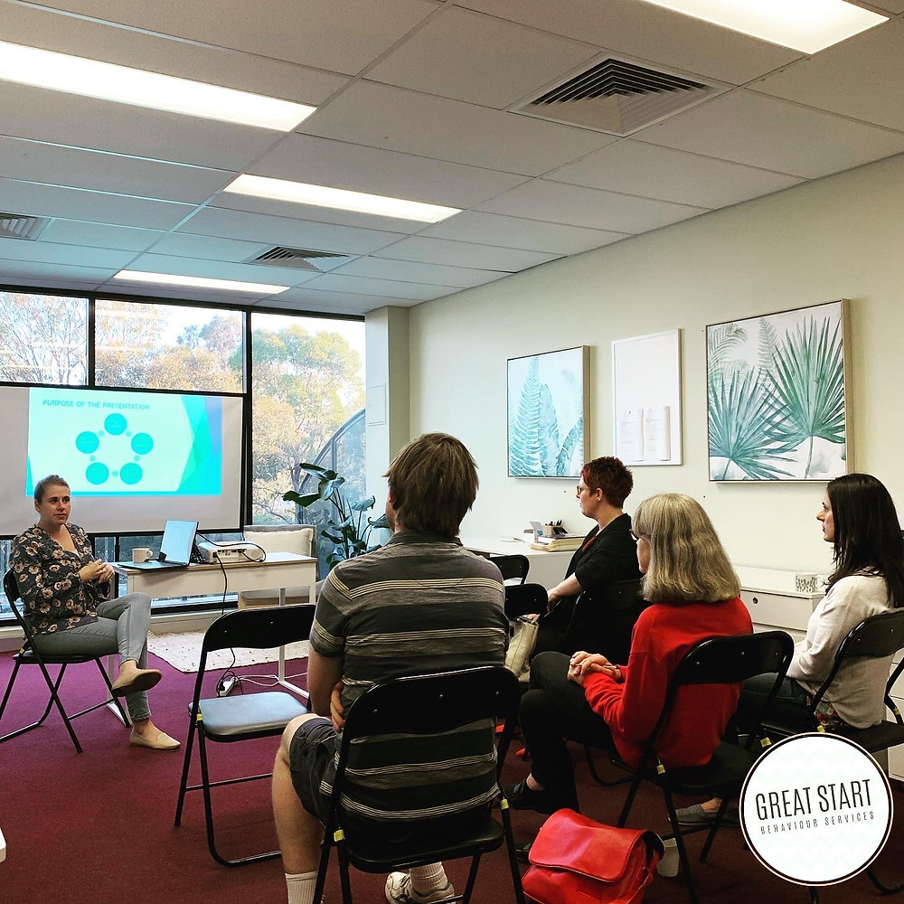 Photo of a woman sitting and lecturing to a group of adults who are also sitting. They are in an office and there is a presentation on a screen in the background.
