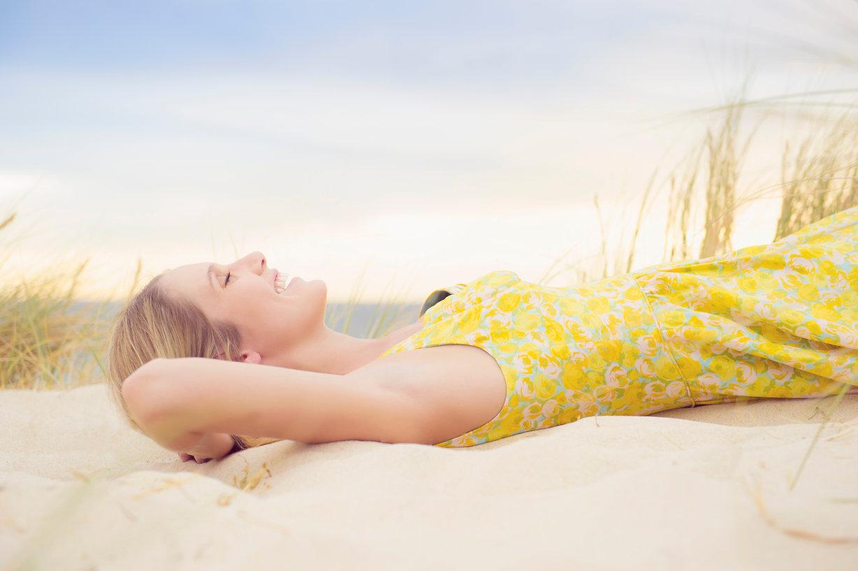 Caucasiano-woman-laying-on-duna de areia