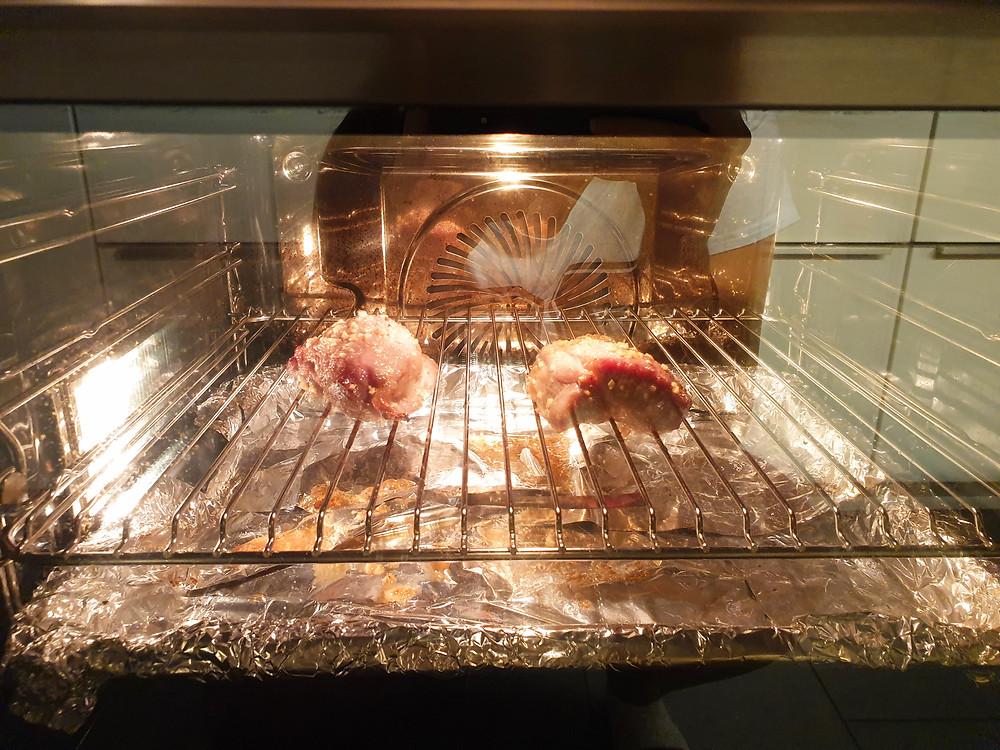 Das Fleisch wird im Backofen auf einem Gitter oberhalb des in Alufolie gewickelten Backblechs mit Wasser platziert.