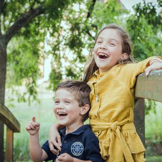 Deux enfants qui rient sur un pont en bois  au parc de la Morinière à Rezé