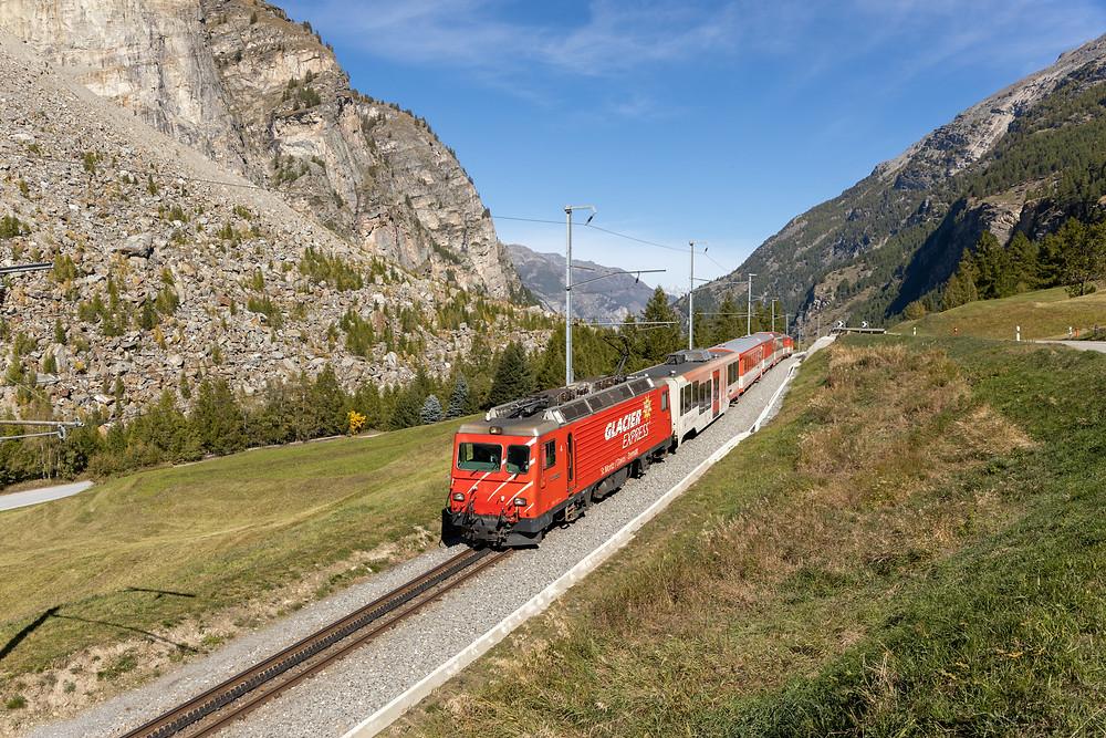 MGB Matterhorn Gotthardbahn HGe 4/4 II mit der Glacier Express Werbung zieht einen Regio bergwärts Richtung Zermatt, aufgenommen in Randa, Wallis, Schwiez.