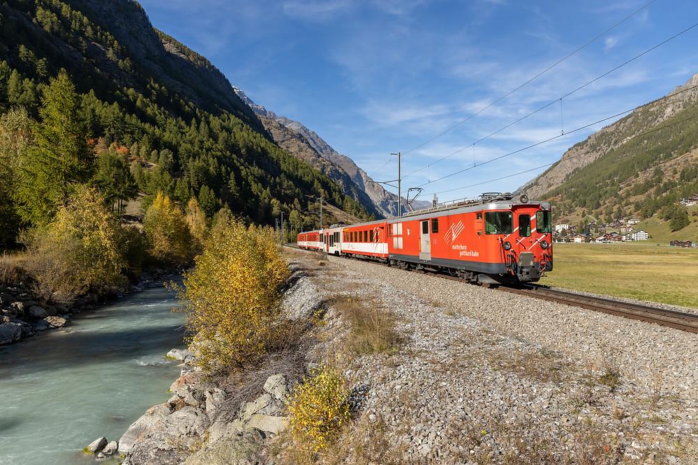 MGB Matterhorn Gotthardbahn Deh 4/4 Typ BVZ fährt entlang der Mattervispa Richtung Zermatt, aufgenommen in Täsch, Wallis, Schweiz