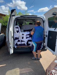 A woman looking in the rear open doors of a van containing humane animal traps for a trap, neuter, return, manage event for over 200 cats in Waianae, Hawaii