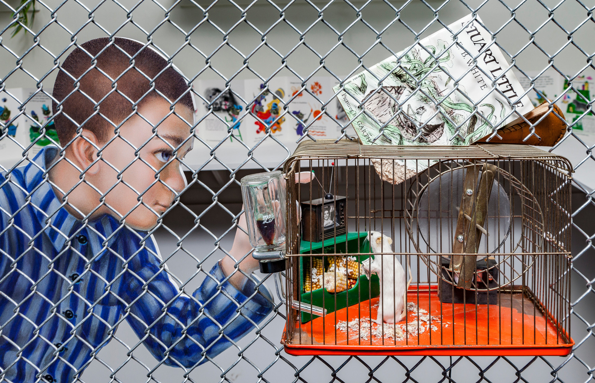 The life-sized figure of the boy that is part of this tableau continues the theme of incarceration in his shirt's vertical stripes, reminiscent of the garb worn in the concentration camps.   In direct opposition to the warning signage, the boy is sticking his index finger of his left hand is poking into the cage of the mouse, the implicit danger is that it will be gnawed on like the book Stuart Little that is the featured altered book, altered by the fact of its being gnawed on by the cage's inhabitant. It appears that the mouse has pulled the bottom of the book into his cage and gnawed on it because the floor of his cage is littered with book debris.  Stuart Little is the altered book that functions as the lead-in to the Animal Friends tableau. It's installed directly in the chain link fence and can be viewed both from the exterior and the interior. Also, it's a cage within a cage and in that sense is a metaphor for the larger tableau.