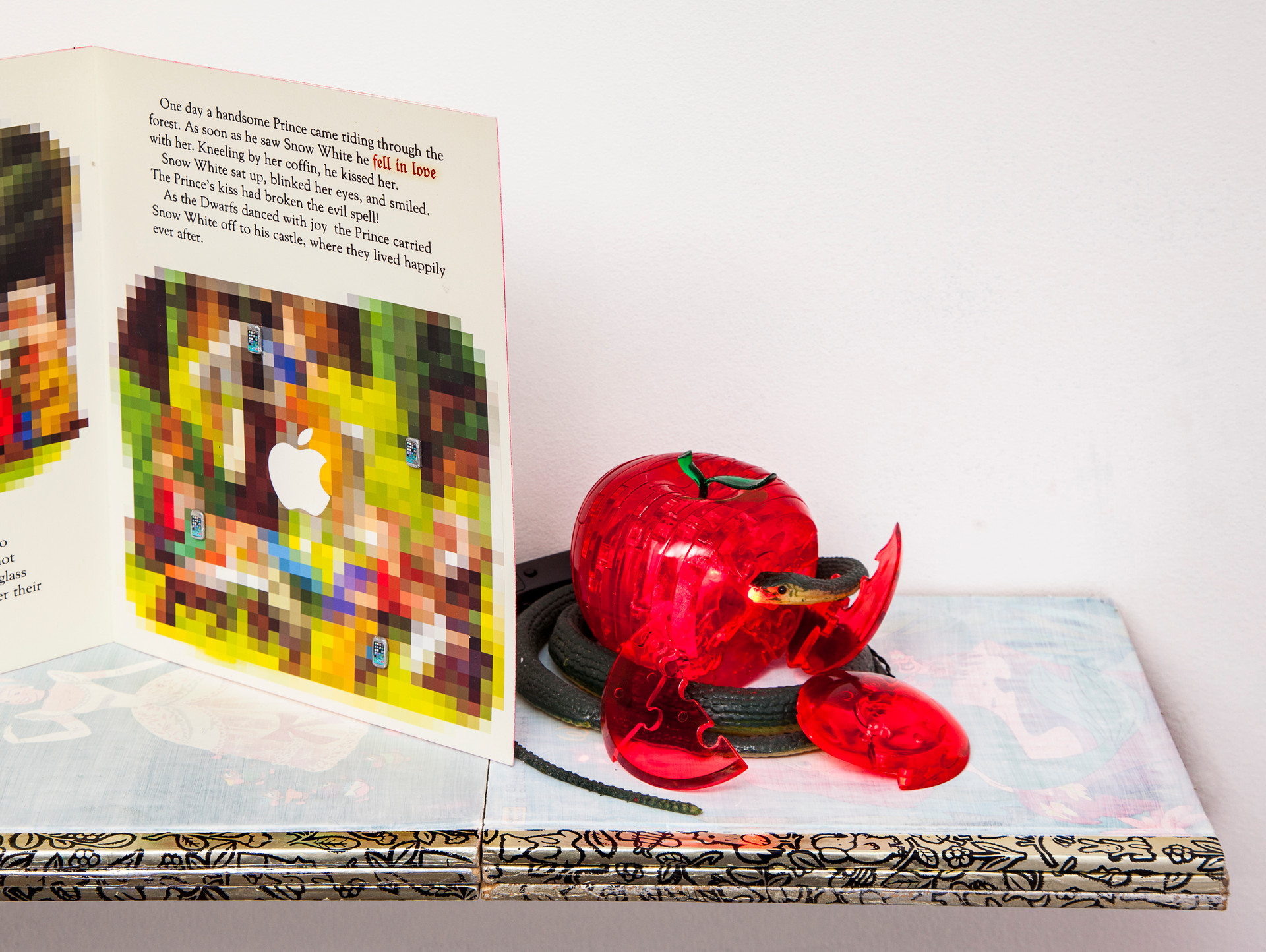 Last page of book totally pixelated except for Apple computer logo that dominates center. To right, red plastic apple is in process of deconstructing. Rubber snake with LED-lit mouth surrounds apple.