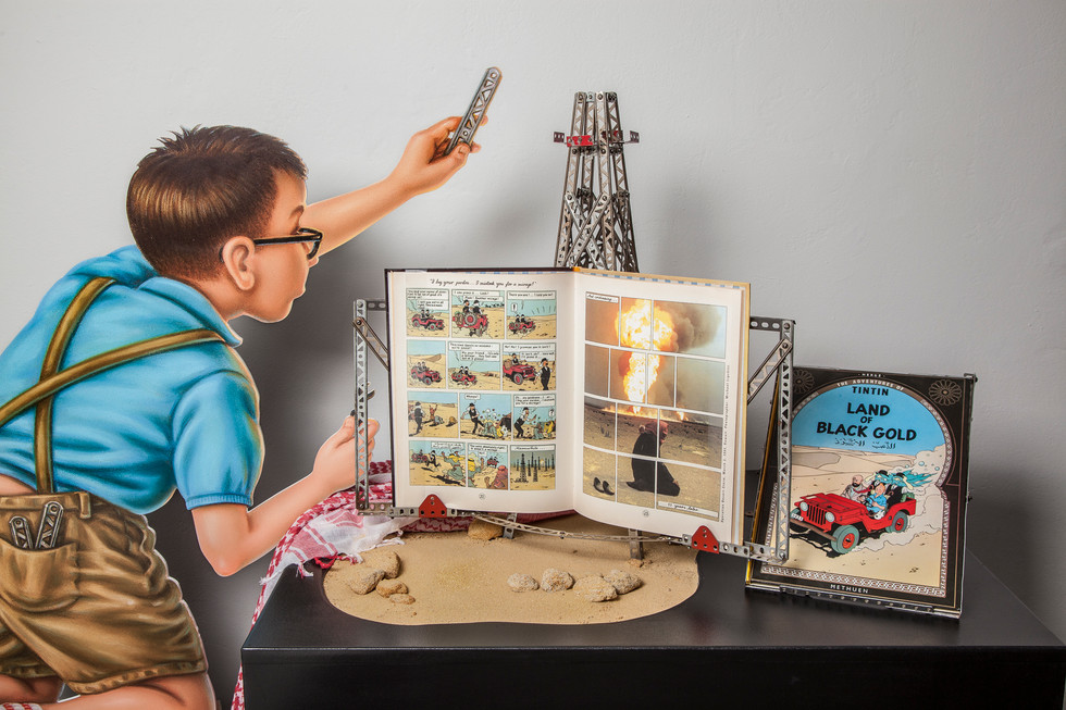 """Altered page spread from """"Adventures of Tin Tin: Land of Black Gold"""" by Hergé, 1950. Unaltered book to right. Two bookstands constructed of Erector Set parts. Sand, accented with gold glitter, fills biomorphic recess (1/4"""" deep) on top of higher pedestal."""