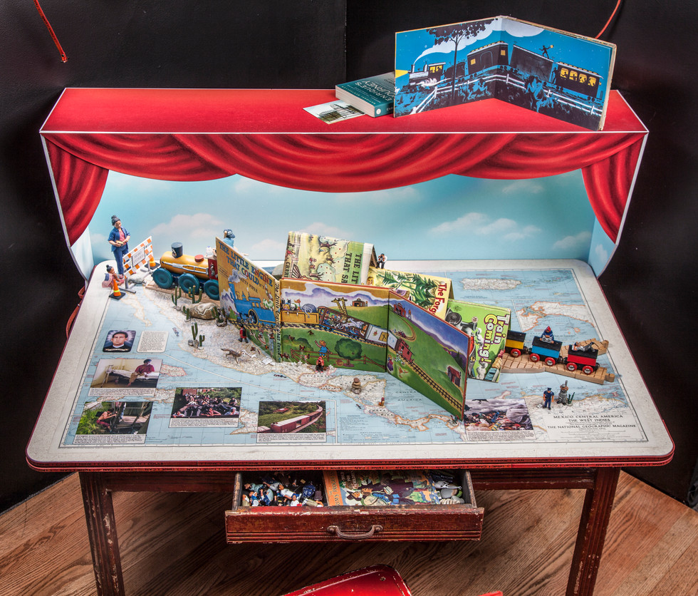 The alteration of the book consists of a combination of inside and outside covers to create the landscape through which the little boy travels. The initial title has been colored so that it also reads The Little Niño that Couldn't.  As the train travels from downstage right to upstage left, the scale of the toy train and figures change from smaller to larger. The change in scale coincides with a transition in geography (from Central America to North America) in the map below, and a change in time (past to the future).