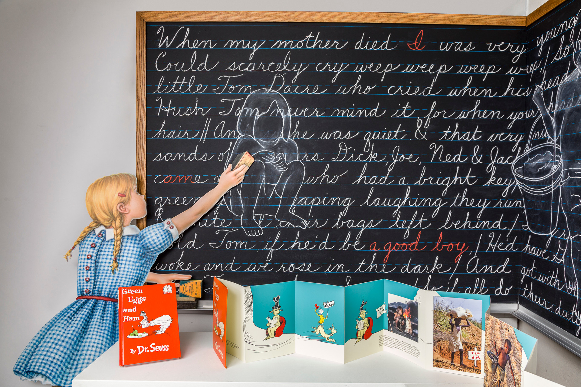 """1950s girl with eraser standing on pile of Dr. Seuss books in process of collapsing. Written on blackboard is """"The Chimney Sweeper"""" by William Blake, 1789. This poem from Blake's Songs of Innocence and Experience focuses on an egregious example of child labor in 18th century London. Three life-size silhouettes drawn over the text are enlarged from photographic images in book below."""