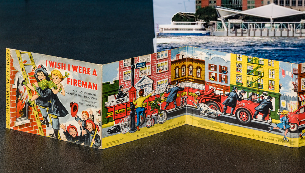 (Pages 1-3.) Cover of I Wish I Were a Fireman depicting heroic child-fireman rescuing adoring girl in green dress with blonde pigtails tied with green bows. First two pages of book follow with horizontal accordion fold-out format reiterating the vertical collapsing format of the South Tower in the background.