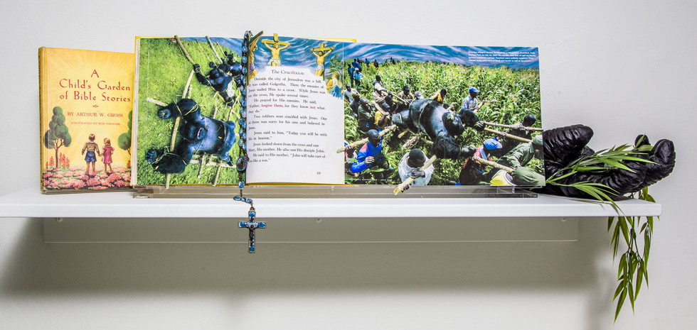 Text of book, A Child's Garden of Bible Verses, is integrated with photographic images from July 2008 National Geographic Magazine of bodies of mountain gorillas killed by Congolese poachers. Carried aloft on scaffolding by grieving villagers they bear an uncanny resemblance to the book's illustration of three victims of crucifixion. Blue rosary beads with black Jesus on cross functions as bookmarked. Life-size rubber gorilla hand projects from back right side of book. Gorilla hand clutches bamboo as in the National Geographic photo.