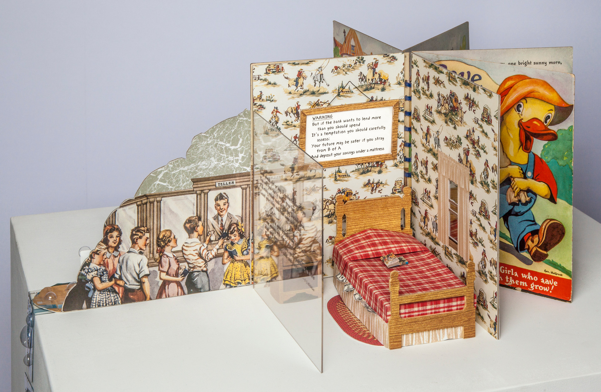 """Moral of altered version is hanging in frame above child's bed. As per this """"Warning,"""" money is stored under the mattress as opposed to in the bank. [All furniture and fabric in this mini tableau has been purposely constructed of paper so as to integrate with book's materials.]"""
