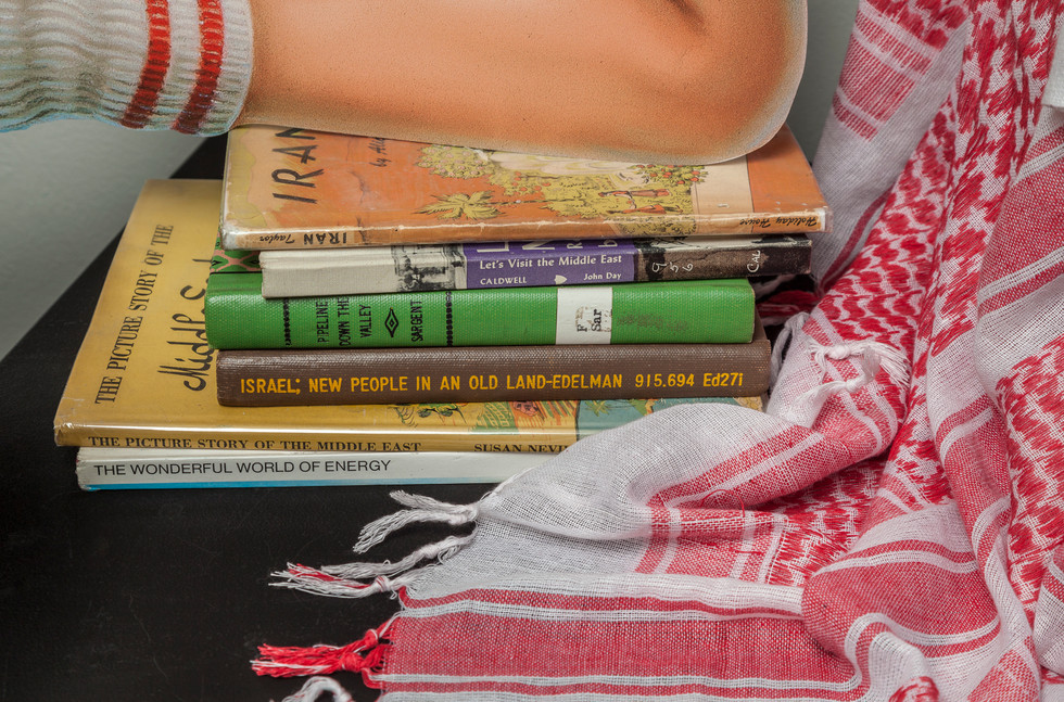 Six decommissioned kids' library books on Middle East resting on pedestal covered with red and white checkered keffiyeh. The keffiyeh matches those of Arabs pictured in Hergé's book as well as that in Lipschitz's photo.
