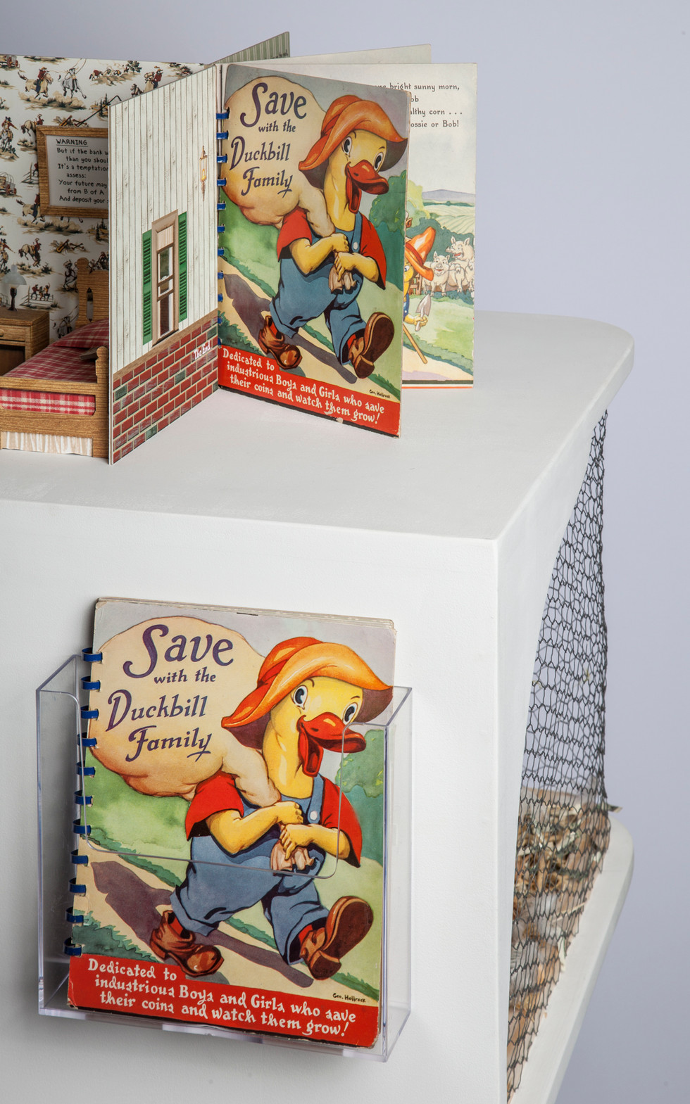 """The altered book is a mid-20th century child's savings book that actually holds coins. These books were given away at banks; and after the book was filled, the child ostensibly could return it to the bank and open a savings account. (Copy of unaltered book on side of pedestal).   The book is spiral bound and arranged in an axial format and is intended to be """"read"""" in a counter-clockwise direction."""