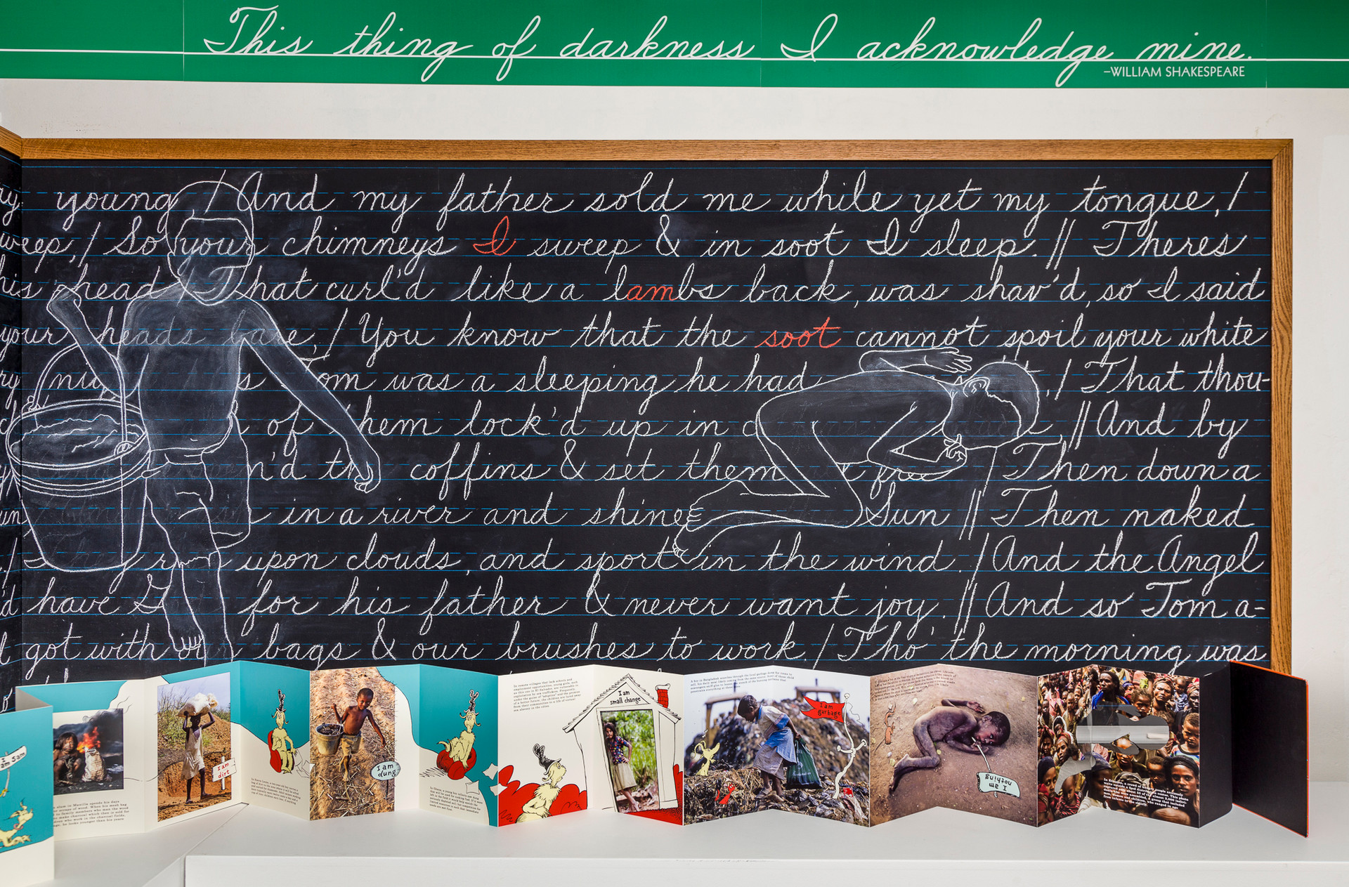The green cursive script above the blackboard is a quote from Shakespeare's The Tempest, specifically words spoken by Prospero to acknowledge Caliban as his slave. In the context of the tableau, however, the phrase is used in a more metaphorical sense as it relates to the light and dark aspects of human nature as well as racial differences. In Blake's poem the polarity of black and white/good and evil is also a strong theme.