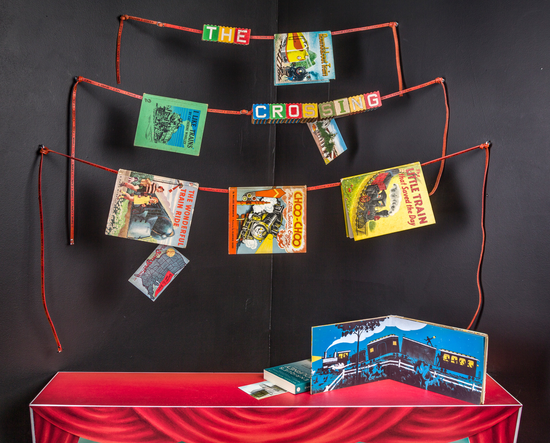 """Hanging from red leather straps that read """"I think I can, I think I can…"""" are children's book about trains, the title of the piece is spelled out in vintage children's blocks. Formally, the diagonal placement of the straps function as a precursor to the diagonal positioning of the table."""