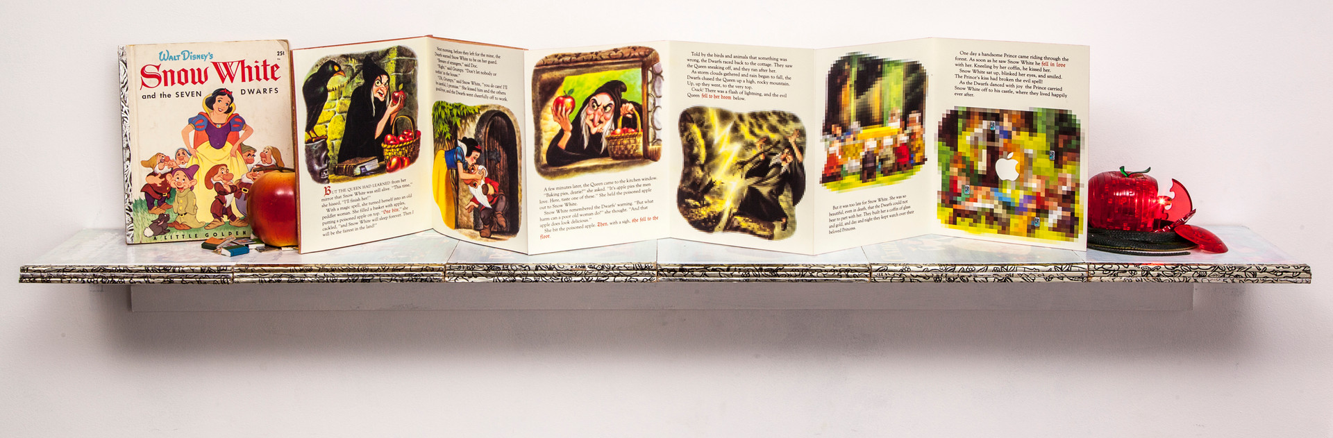 Altered book, Walt Disney's Snow White and the Seven Dwarves, is displayed on shelf formed by eighteen laminated and whitewashed Walt Disney Golden Books. From left to right, book's illustrations become increasingly pixelated.