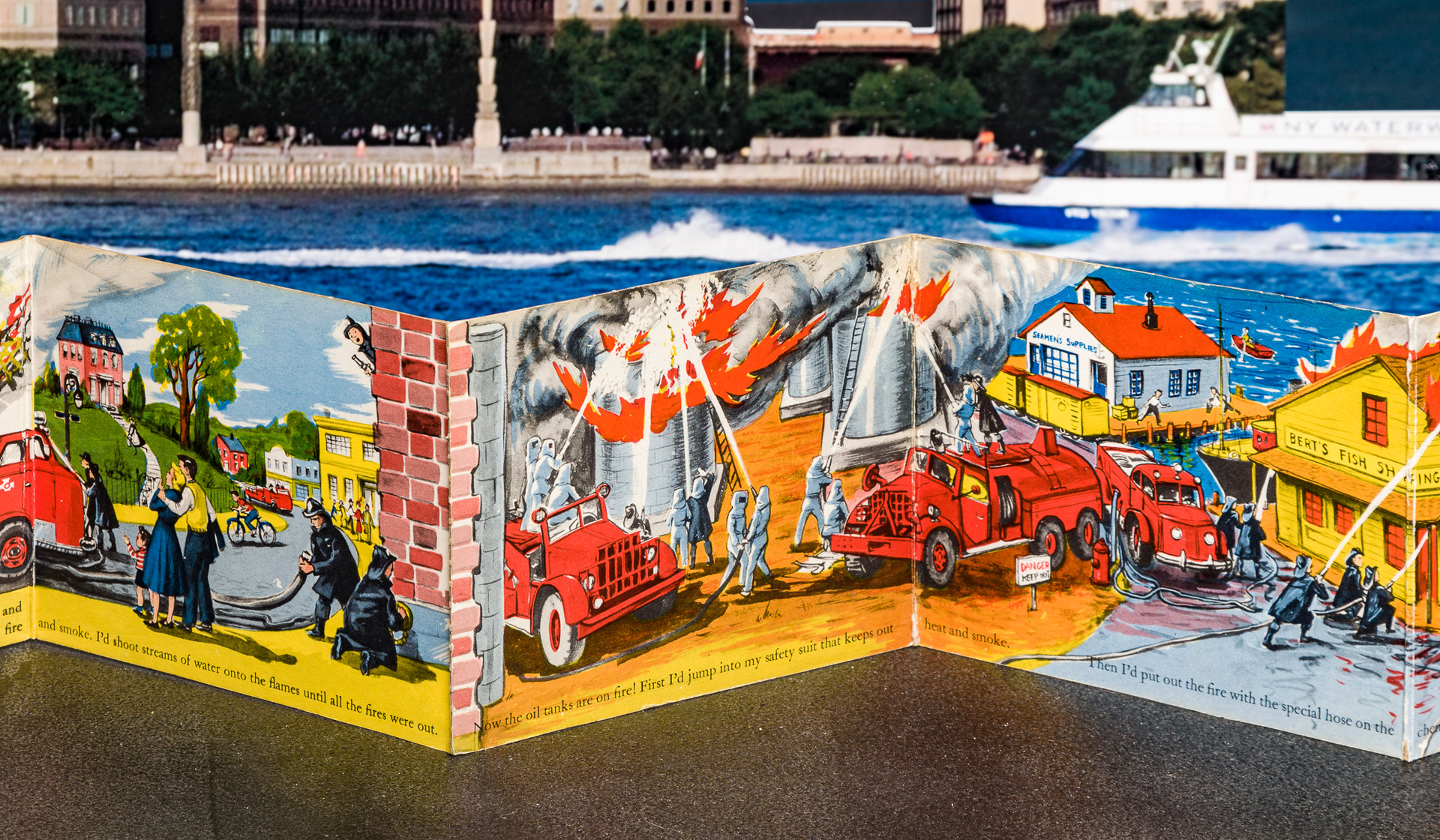 (Pages 7-9.) Fire now has spread to the urban waterfront. Water pictured at top of page 9 helps visually integrate book with tableau panel directly in back picturing Hudson River.