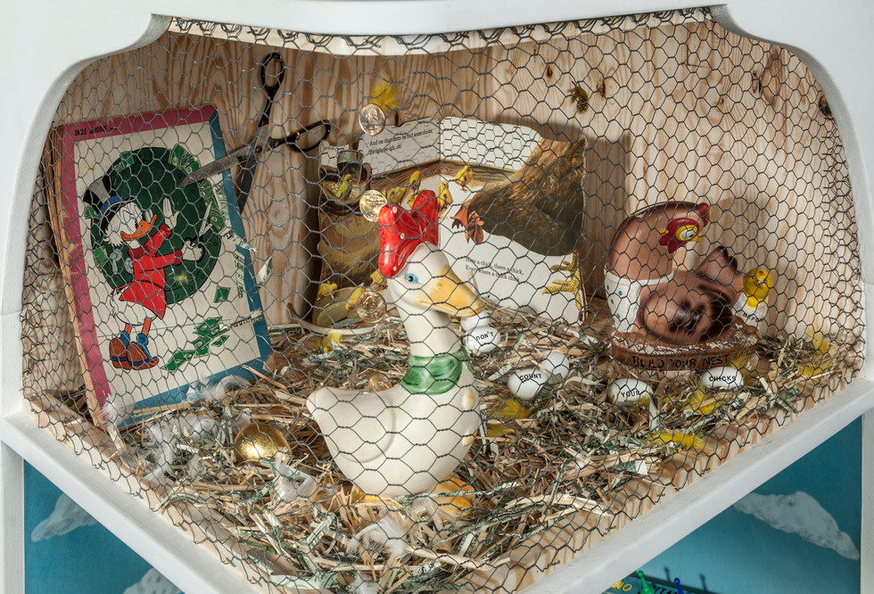 """There are two shelves on the cabinet below the altered Duckbills book. Both shelves combine the barnyard and money themes with vintage 3-D objects arranged in tableaux. The upper shelf features poultry, thus relating to the Duckbill family. The goose on the left was a bank; and it appears to have laid the proverbial golden egg. A string of gold coins hang from the ceiling and descend into the slotted opening on its back. On the right is another bank in the form of a chicken. The chicken has laid white eggs on which are written: """"Don't/count/your/chicks/before….""""   In the back right corner is occupied by an opened child's book, Old MacDonald's Farm. [The 1/2""""-gauge chicken wire pictured in the book is the same gauge as the real wire that encloses the front of the shelf.] In the far left corner is a vintage comic book featuring a large cartoon image of Scrooge McDuck using scissors to trim the paper money that extends from a closed safe. A pair of real scissors hanging on the wall nearby appears to cut the comic book. On the floor of the shelf is a combination of straw, shredded paper money and white and yellow poultry feathers. The walls are covered with faux plywood paper."""