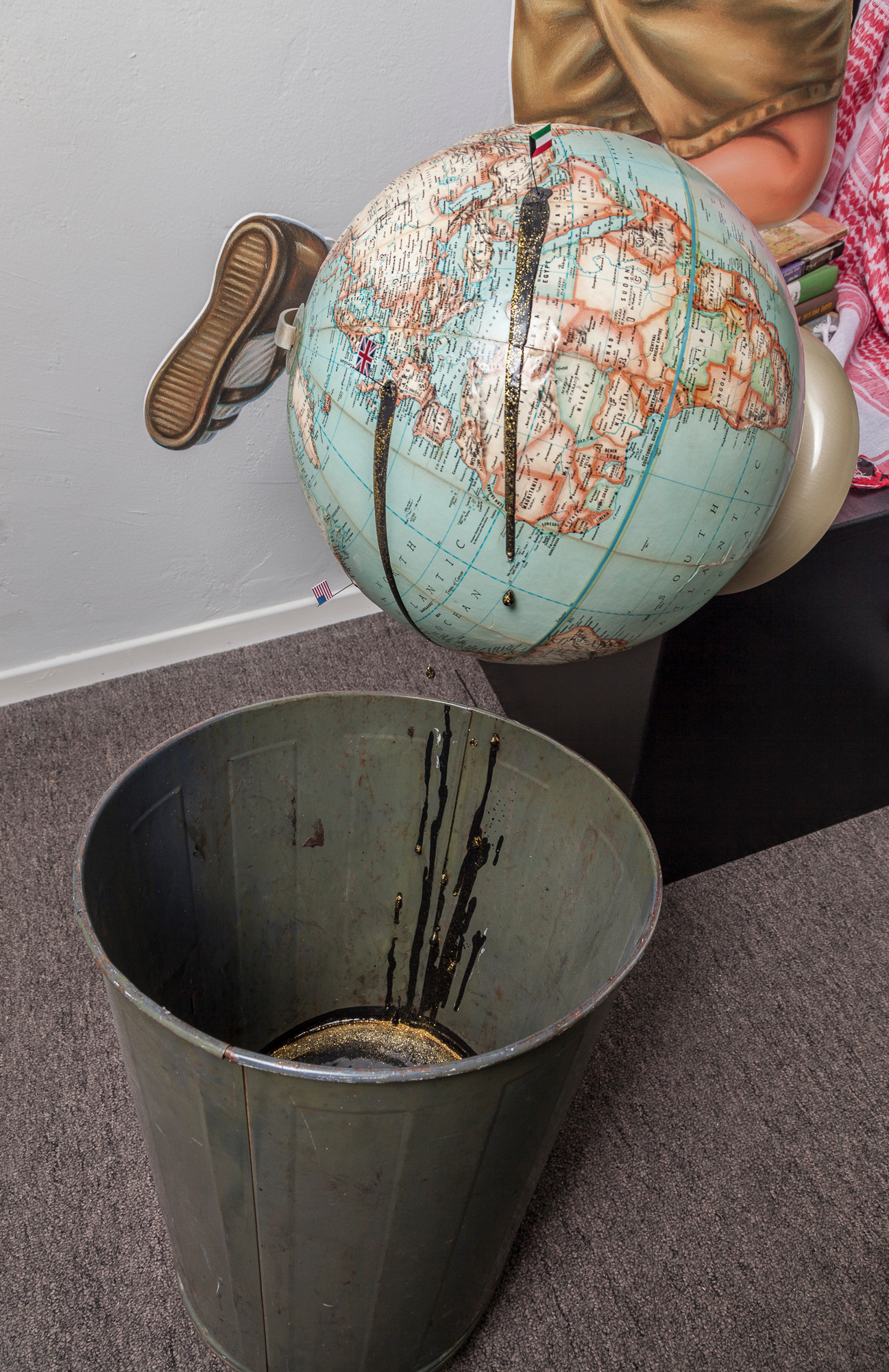 "Vintage classroom globe with miniature flags marking U.S., U.K., and Kuwait. ""Oil"" dripping from flags marking these nations into metal trash can (black acrylic paint, gold glitter, beads on monofilament). Drips continued on side of can; bottom partially filled with black resin and glitter. Vintage classroom globe with miniature flags marking U.S., U.K., and Kuwait. ""Oil"" dripping from flags marking these nations into metal trash can (black acrylic paint, gold glitter, beads on monofilament). Drips continued on side of can; bottom partially filled with black resin and glitter."