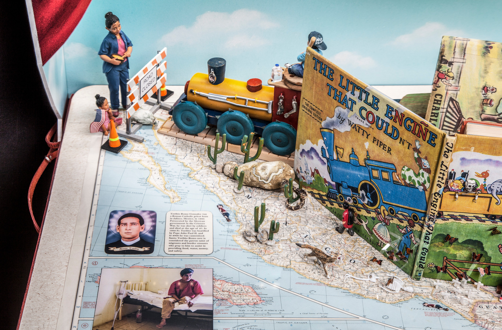 """The train approaching the end of its journey in North America. The mother awaits the boy riding on top of the train's engine. The boy carries a gallon of water, a cell phone, and baseball bat, and wears a hat that reads """"No Fear"""". The engine is decorated with milagros and a crutch; its wheels are inset with X-Acto knife blades, all signifying perils of this journey in which many of the riders lose limbs."""