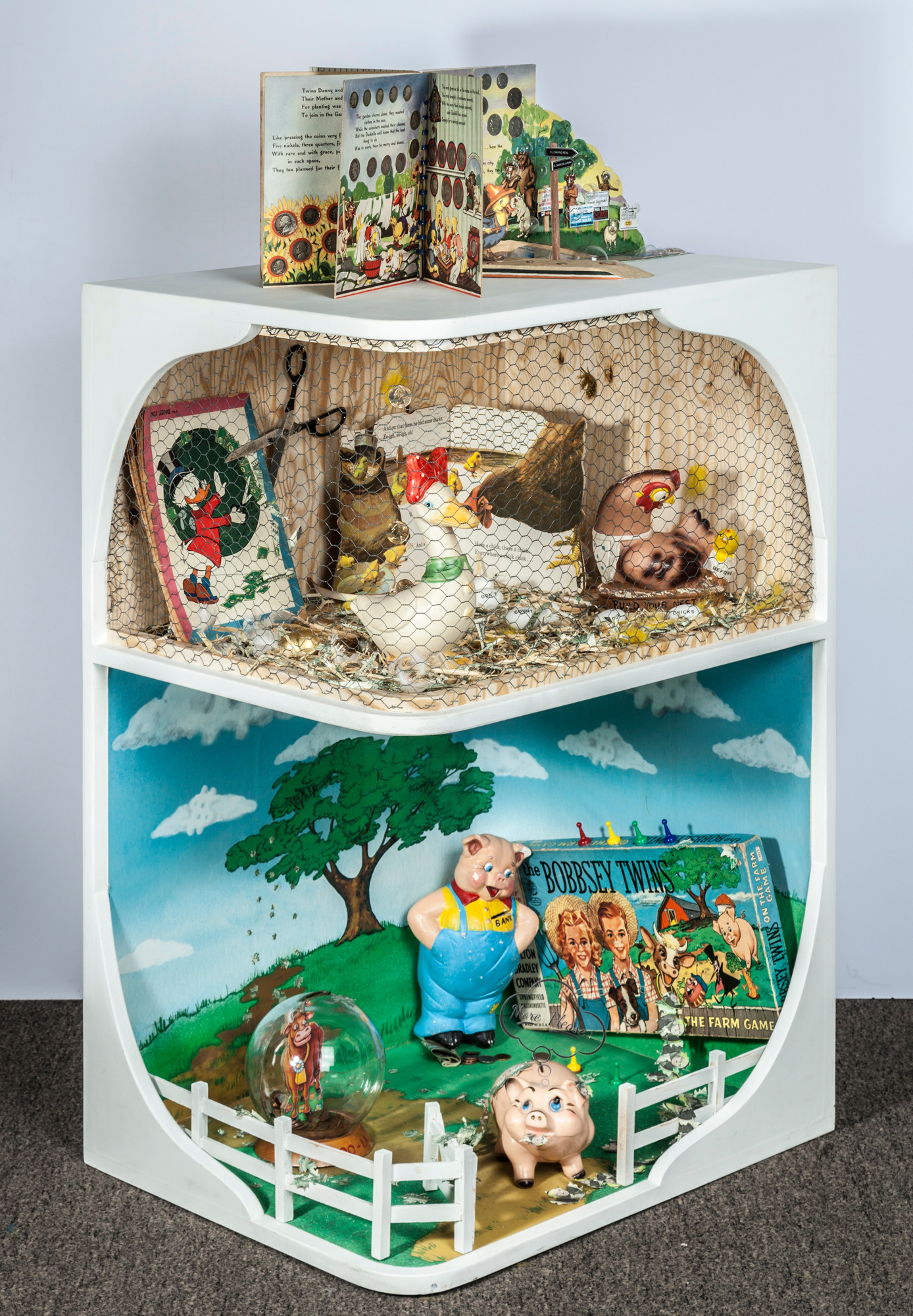 This piece consists of a three part cabinet with the altered book, Save With the Duckbill Family, displayed at the top. The dual theme of farming and money is continued on the two shelves below in vignettes composed of vintage three dimensional vintage objects from the 1950s.