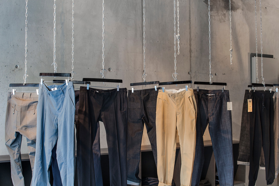 Jeans and pants hanging from chains in concrete wall