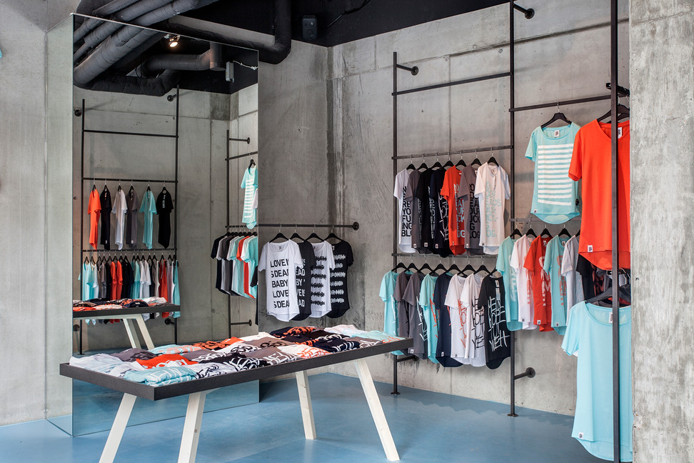 Colorful t-shirts hanging in Berlin industrial looking fashion shop