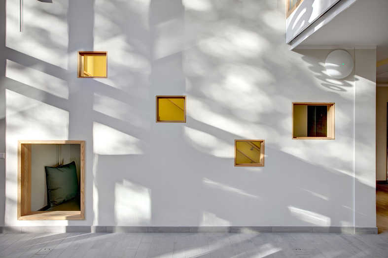 White wall with different-sized indoor windows and sun reflections