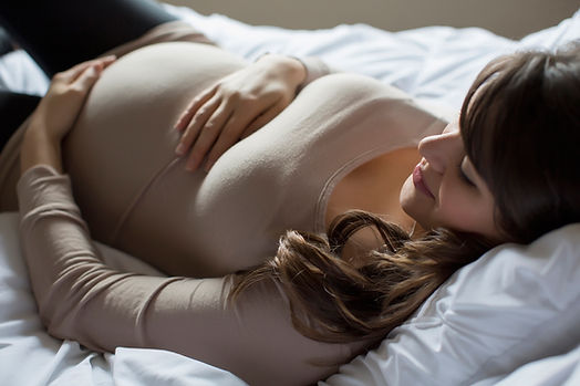 A pregnant woman with long brown hair reclines on a white doona with white pillows. She's wearing a yoga outfit and smilin.