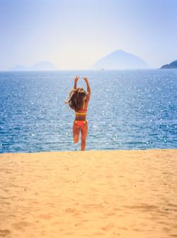 Bigstock_ 73439132 - Blonde Slim Girl In Bikini Runs From Sea On Sand Laughs