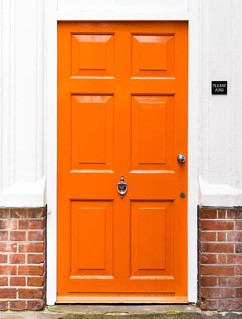 Single%20bright%20orange%20painted%20wooden%20door%20with%20red%20brickwork%20and%20white%20walls_ed