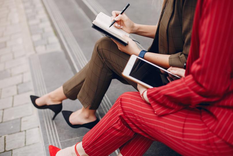 two-businesswomen-working-in-a-city-BXLQ