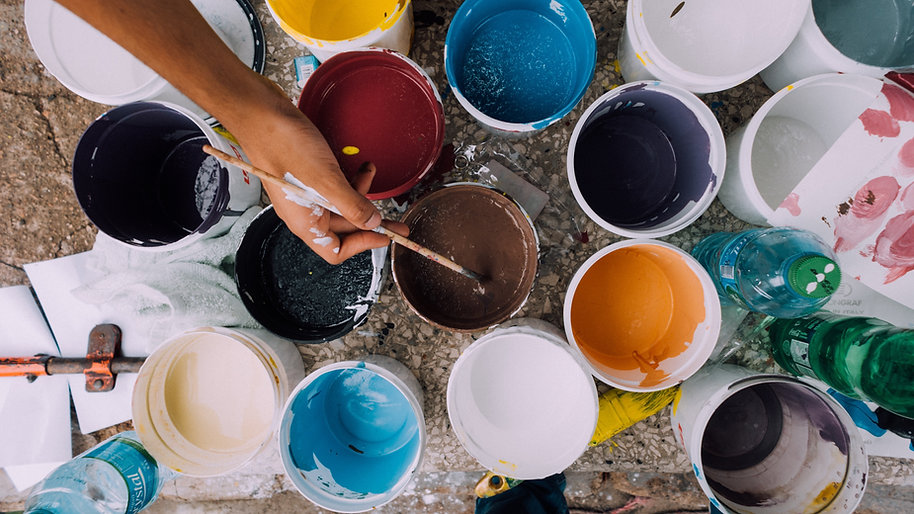 A hand holding a paintbrush over tubs of different colored paints
