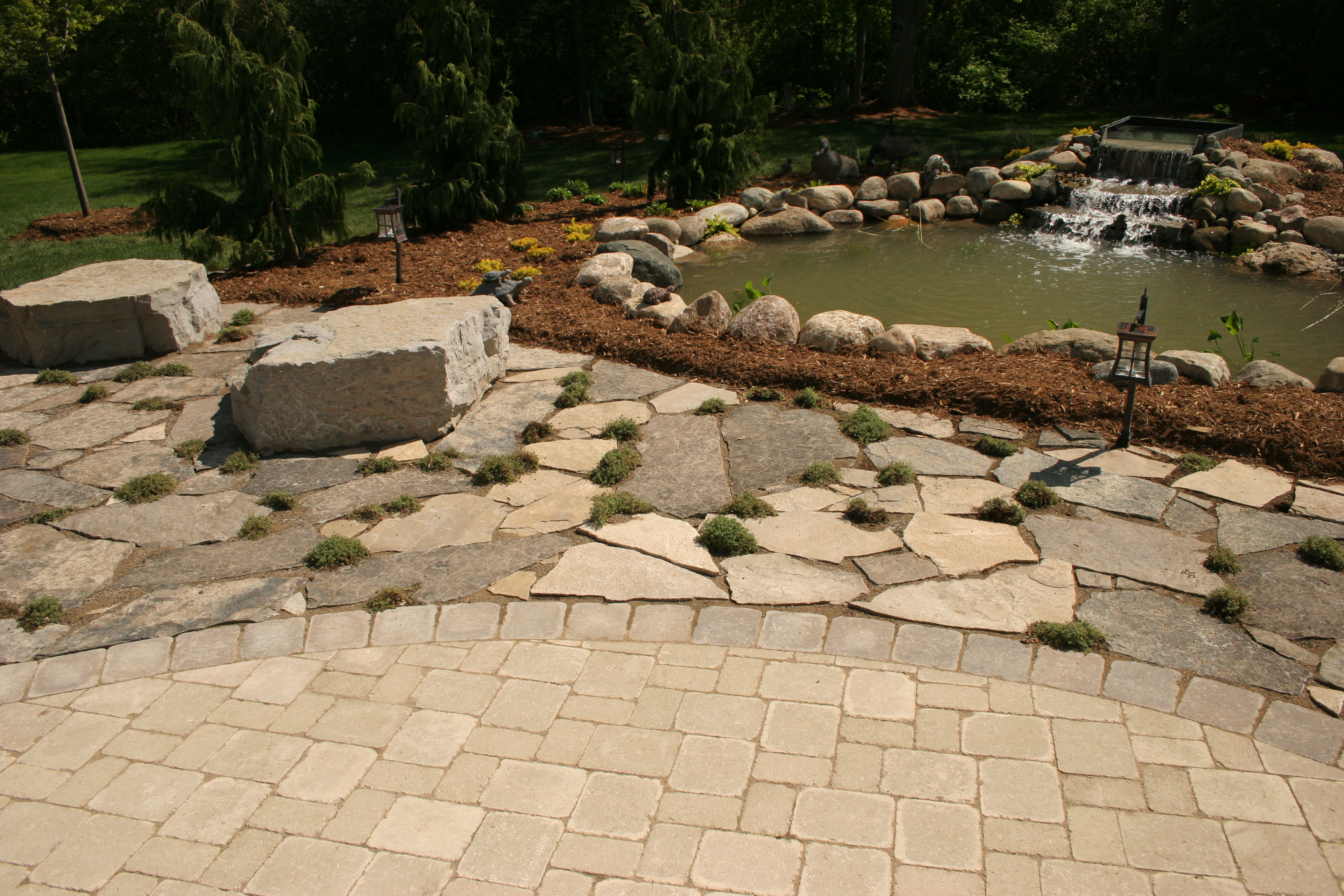 Brick Paver Patio and Flagstone Patio With Pond And A Waterfall By All Terra Landscape Services Of L