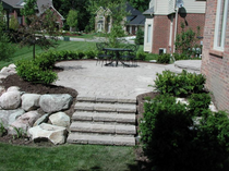 Raised Brick Patio With Boulder Retaining Wall