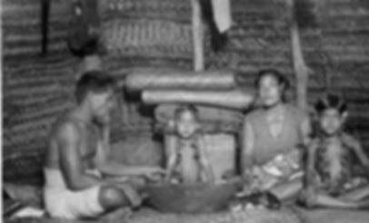 America Samoa family insde a family fale wit woode serving bowl and lowered blinds (pola). Circa 1940