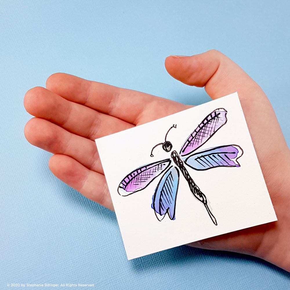 Child's hand holding a small dragonfly painting.