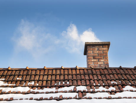 Smoke raising from a chimney in winter.j