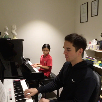 Adam is demonstrating and teaching on a modern full lengthed piano for easier and efficient teaching.