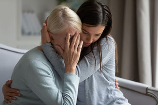 Empathic young lady embracing soothing crying depressed elder mommy, sitting together at